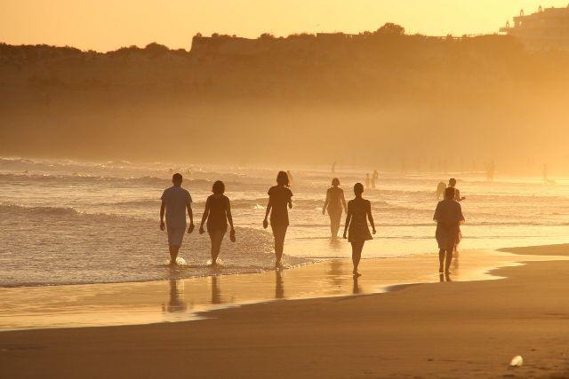 さまざまバックグラウンドがある人達がビーチを歩いている画像