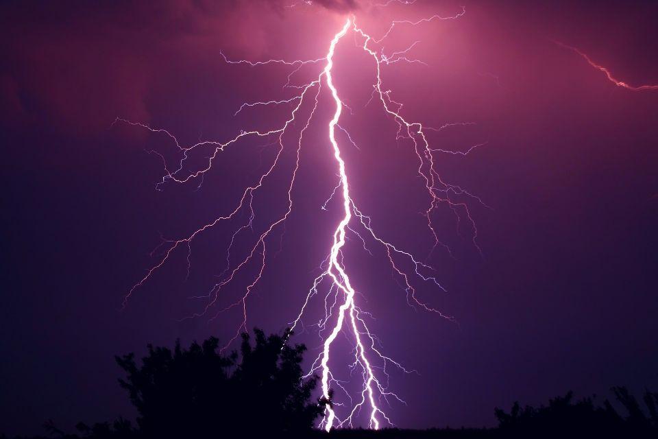 紫色の空に一閃の雷が落ちるイメージ画像